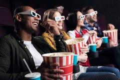 amis de sourire en verres 3d avec le maïs éclaté et le film de observation de soude Image libre de droits