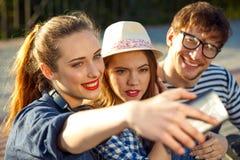 Amis de sourire faisant le selfie dehors Photos stock