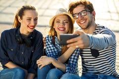 Amis de sourire faisant le selfie dehors Photographie stock libre de droits