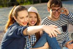 Amis de sourire faisant le selfie dehors Photo stock