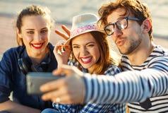 Amis de sourire faisant le selfie dehors Image stock