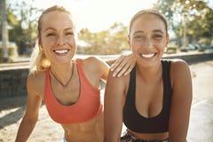 Amis de sourire faisant une pause de leur séance d'entraînement extérieure images stock