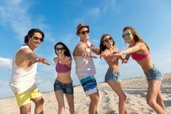 Amis de sourire gais ayant l'amusement sur la plage Photo libre de droits