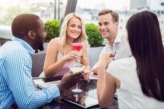 Amis de sourire gais s'asseyant dans le café Photos stock
