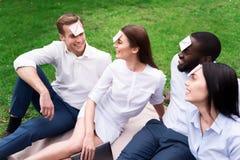 Amis de sourire gais se reposant sur la couverture Image stock