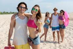 Amis de sourire gais se reposant sur la plage Image stock