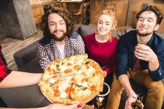 Amis de sourire goûtant la pizza Photo stock