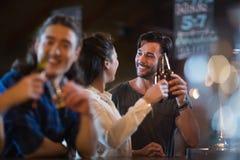 Amis de sourire grillant des bouteilles à bière Photos libres de droits