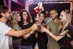 Amis de sourire grillant des verres de bière avec l'interprète chantant à l'arrière-plan Images libres de droits
