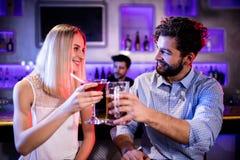 Amis de sourire grillant le verre de cocktail et de bière au compteur de barre Images libres de droits
