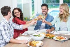 Amis de sourire grillant le vin blanc Photos libres de droits