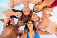 Amis de sourire heureux à la plage Photos stock