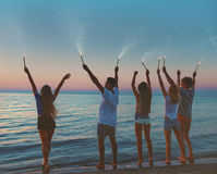 Amis de sourire heureux à la plage avec les bougies de scintillement Photo libre de droits