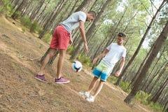 Amis de sourire heureux jouant dans la forêt dehors Photographie stock