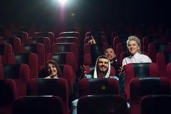 Amis de sourire heureux observant le film dans le théâtre Photo libre de droits