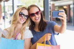 Amis de sourire heureux prenant un selfie Images stock