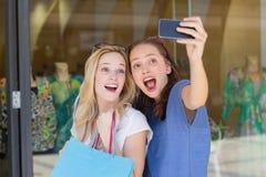 Amis de sourire heureux prenant un selfie Photographie stock