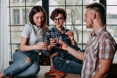 Amis de sourire heureux s'asseyant autour et verres tintants avec d Images stock