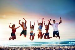 Amis de sourire heureux sautant à la plage Image libre de droits