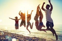 Amis de sourire heureux sautant à la plage Photographie stock