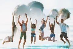 Amis de sourire heureux sautant à la plage Double exposition Image libre de droits