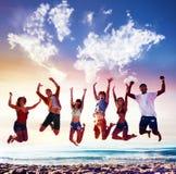 Amis de sourire heureux sautant par-dessus un ciel bleu avec une carte du monde faite de nuages Photos stock