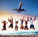 Amis de sourire heureux sautant sur la plage avec un avion sur le ciel Photographie stock libre de droits