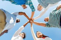 Amis de sourire heureux se tenant dehors en cercle Photos libres de droits