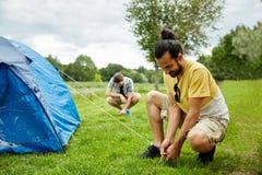 Amis de sourire installant la tente dehors Images libres de droits