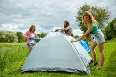 Amis de sourire installant la tente dehors Image stock
