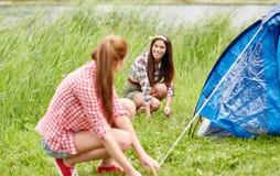 Amis de sourire installant la tente dehors Image libre de droits