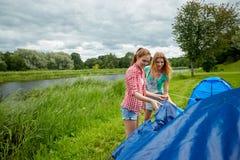 Amis de sourire installant la tente dehors Photo libre de droits