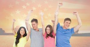 Amis de sourire jetant leurs mains avec un drapeau américain dans le ciel Photographie stock libre de droits
