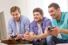 Amis de sourire jouant des jeux vidéo à la maison Photos stock