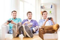 Amis de sourire jouant des jeux vidéo à la maison Photographie stock libre de droits