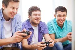 Amis de sourire jouant des jeux vidéo à la maison Image libre de droits
