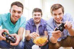 Amis de sourire jouant des jeux vidéo à la maison Photo stock