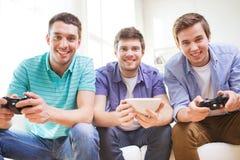 Amis de sourire jouant des jeux vidéo à la maison Image stock