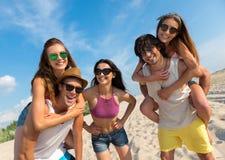 Amis de sourire joyeux ayant l'amusement sur la plage Photo libre de droits