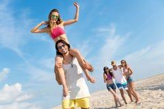 Amis de sourire joyeux ayant l'amusement sur la plage Images libres de droits