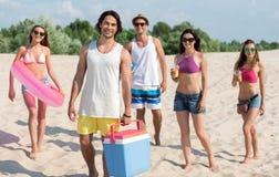 Amis de sourire joyeux se reposant sur la plage Image stock