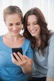 Amis de sourire lisant le message à leur téléphone Photo stock