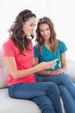 Amis de sourire lisant le message textuel à la maison Image libre de droits
