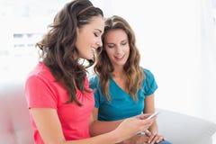 Amis de sourire lisant le message textuel à la maison Photo stock