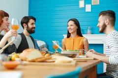 Amis de sourire mangeant ensemble à la maison Images stock