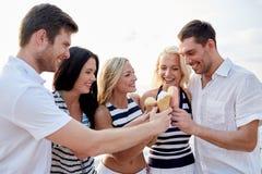 Amis de sourire mangeant la crème glacée sur la plage Image stock