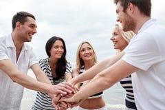 Amis de sourire mettant des mains sur l'un l'autre Photographie stock libre de droits