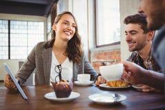 Amis de sourire mettant en oeuvre le café et l'employant au comprimé Image stock