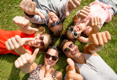 Amis de sourire montrant des pouces se trouvant sur l'herbe Photographie stock