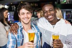 Amis de sourire montrant la bière avec leurs amis Photos libres de droits